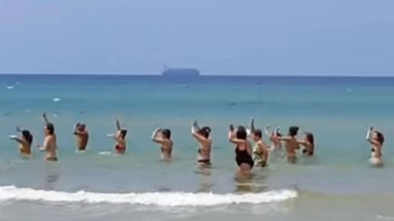 pozzallo, balli di gruppo in spiaggia e sullo sfondo c`è la maersk: è polemica - tgcom24