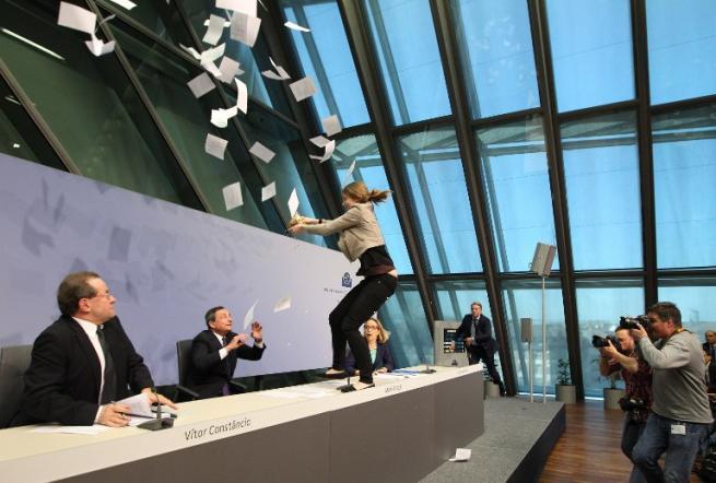 Mario Draghi contestato alla conferenza della Bce: un'attivista gli tira dei coriandoli