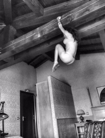 Naike Rivelli in slip e reggiseno appesa a una trave in albergo