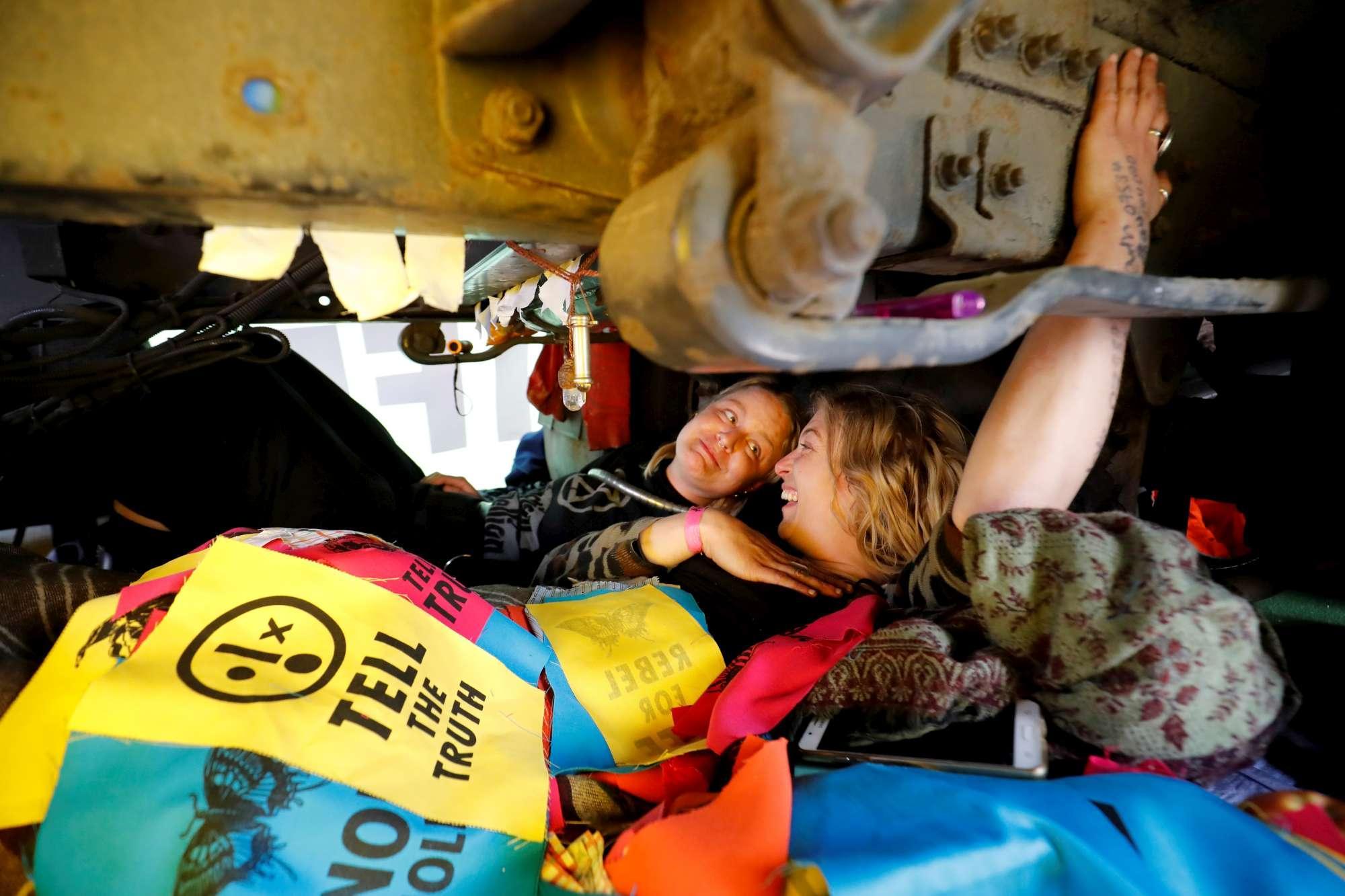 Clima, attivisti scendono in strada a Londra e  si incollano  su un treno per protesta: traffico in tilt