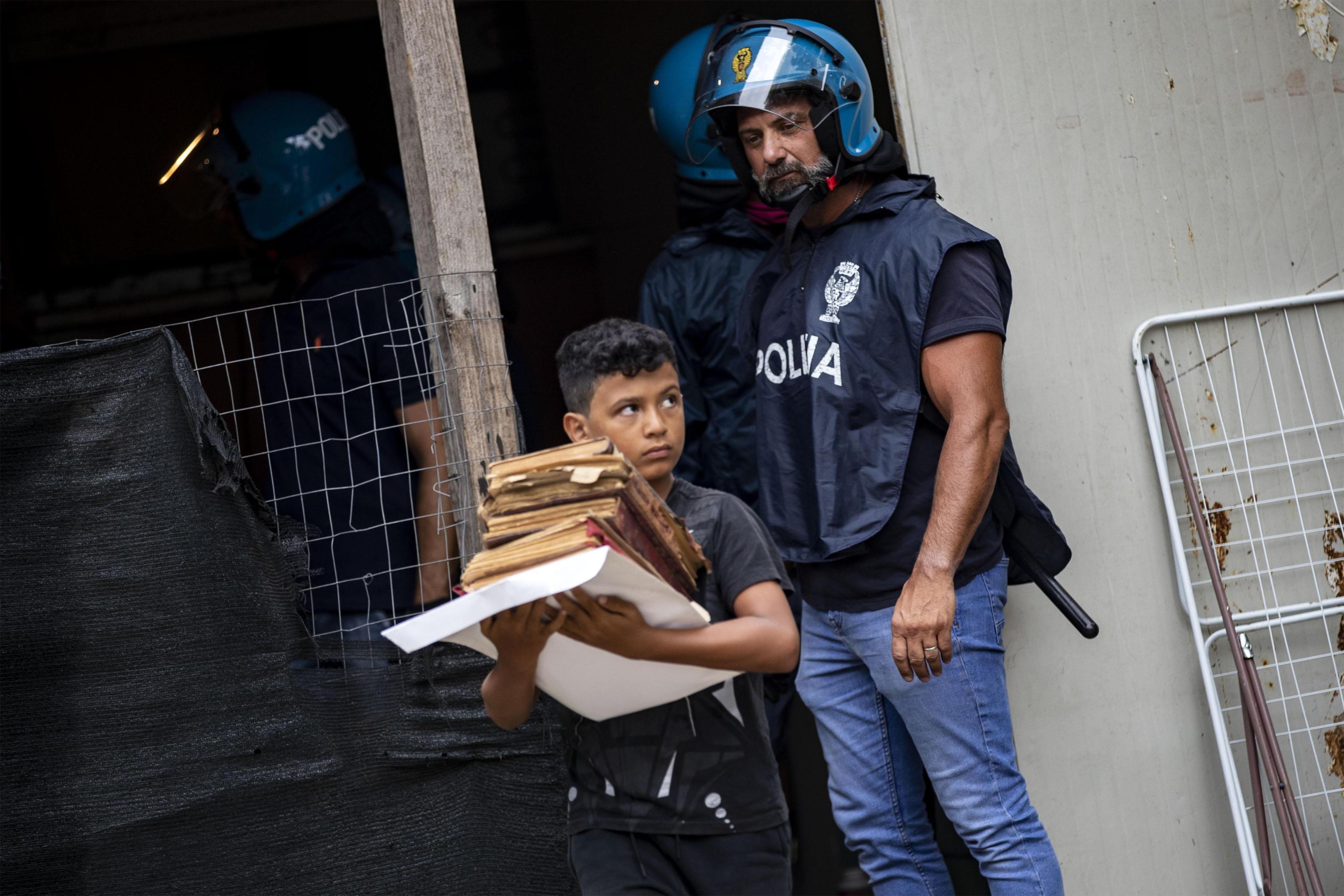 Primavalle, un bambino porta via i libri e il poliziotto lo guarda: la foto simbolo dello sgombero