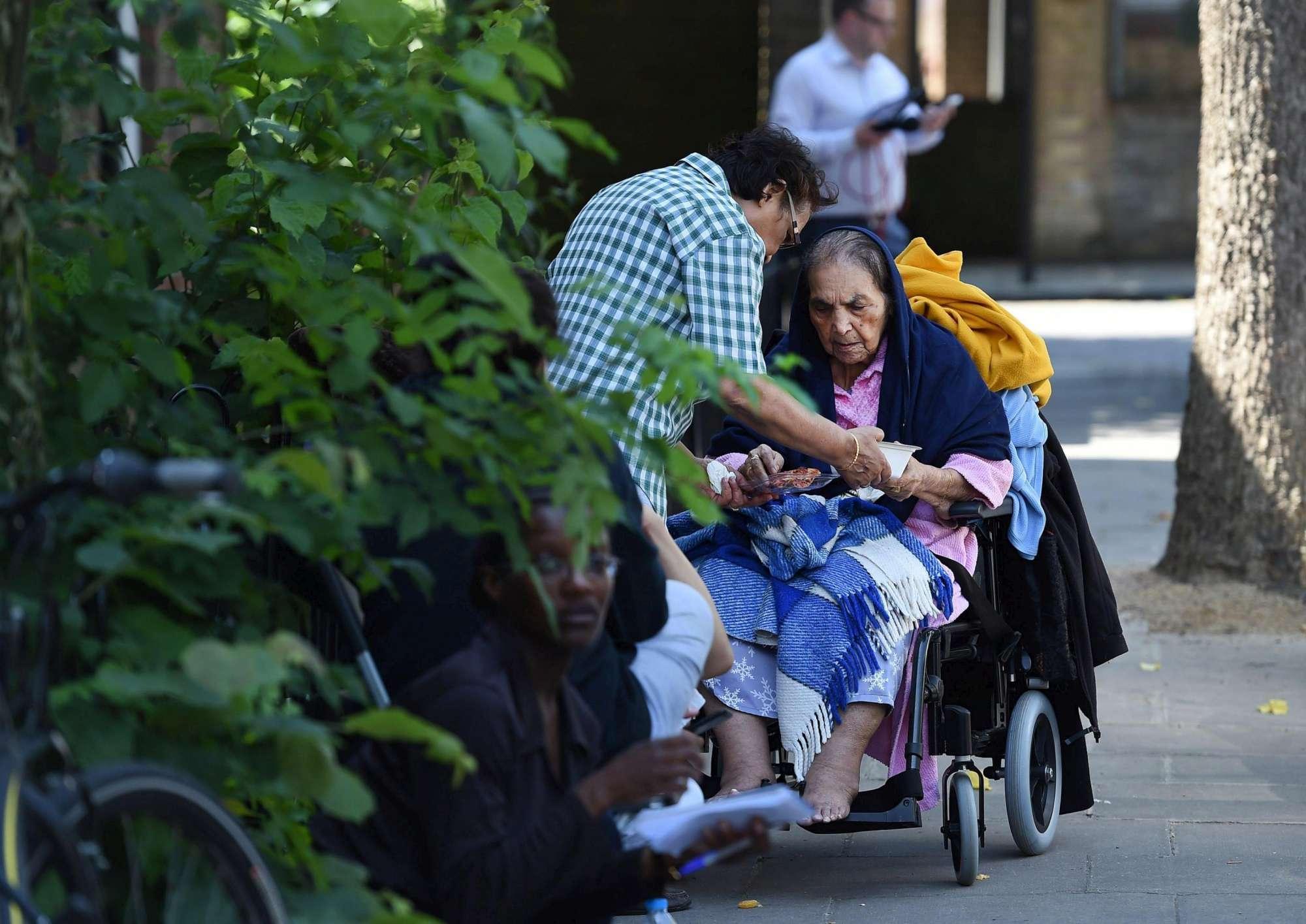 I sopravvissuti, i familiari, gli amici e i volontari: facce e lacrime sotto la torre dopo il rogo di Londra