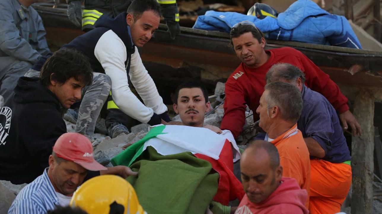 Amatrice: sepolto sotto le macerie, un uomo viene tratto in salvo su una barella avvolto nel Tricolore